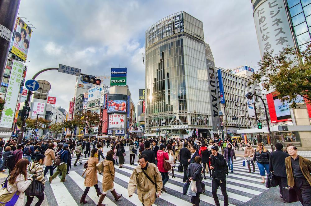 Attraversare l'incrocio di Shibuya guardando lo smartphone