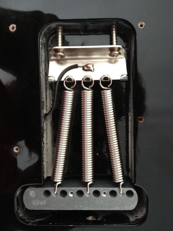 Il retro di un ponte/vibrato tradizionale. Notare le tre molle in estensione: l'unico modo per regolare la tensione è agire sulle due viti. Non certo un'operazione che si può eseguire ad ogni accordatura…