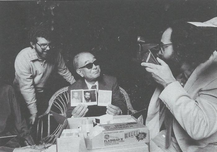 Francis Ford Coppola dimostra il funzionamento del regalo appena fatto ad Akira Kurosawa: una scatola delle nuove pellicole Polaroid Time-Zero sotto gli occhi estasiati di George Lucas