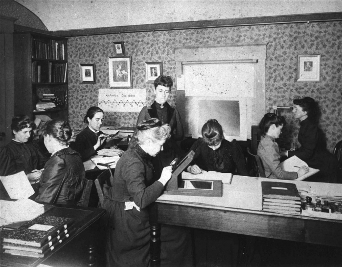 arvard Computers at work, circa 1890, including Henrietta Swan Leavitt seated, third from left, with magnifying glass (1868–1921), Annie Jump Cannon (1863–1941), Williamina Fleming standing, at center (1857–1911), and Antonia Maury (1866–1952).
