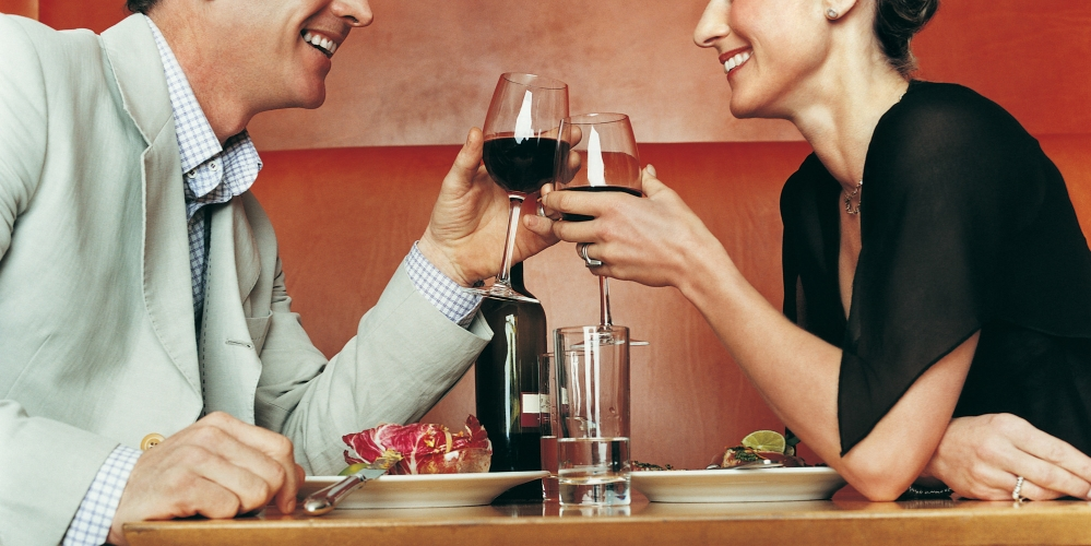 Couple Sitting at a Restaurant and toasting With Red Wine