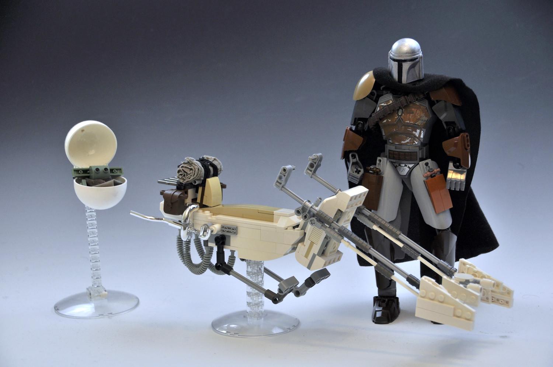 Il mandaloriano in sella alla sua speederbike LEGO accompagnato da Baby Yoda